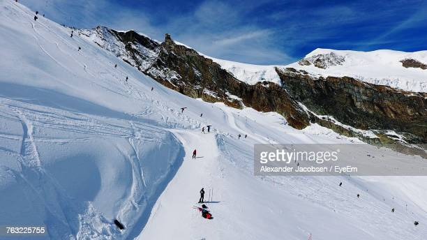Aerial View Of People Skiing On Snow Covered Landscape Against Cloudy Sky