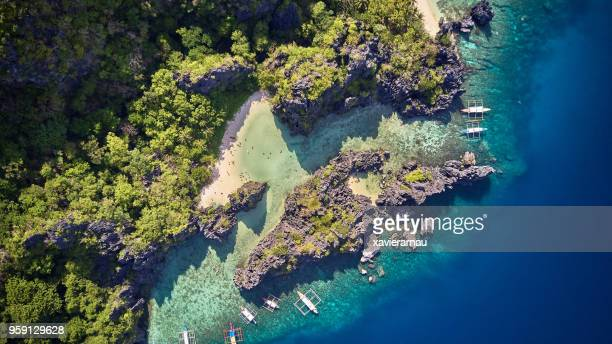 aerial view of people swimming at hidden beach, el nido, palawan, philippines - el nido stock pictures, royalty-free photos & images