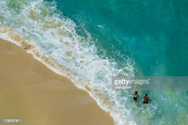 Aerial view of people swimming in the transparent turquoise sea.
