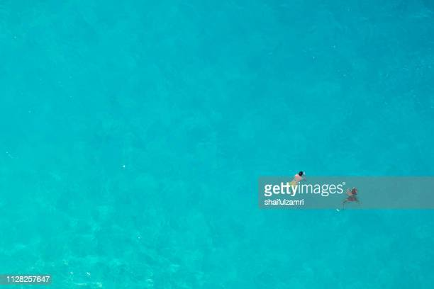 aerial view of people swimming in the transparent turquoise sea. - shaifulzamri - fotografias e filmes do acervo