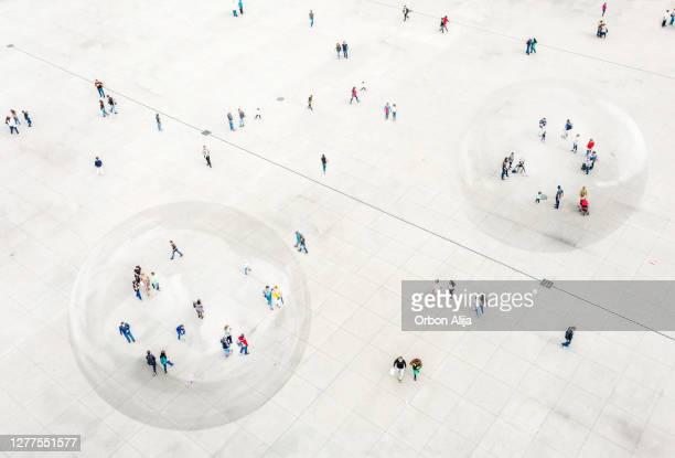 luchtfoto van mensen die in een bel voor covid-19 bescherming lopen. - binnenin stockfoto's en -beelden