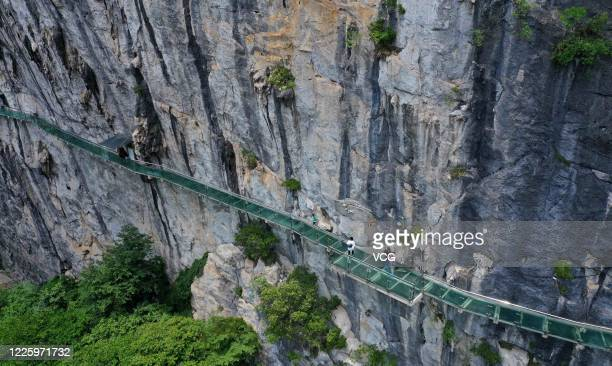 Aerial view of people walking on a glass-bottomed skywalk at Shimen Xianhu Scenic Area on May 19, 2020 in Liuzhou, Guangxi Zhuang Autonomous Region...