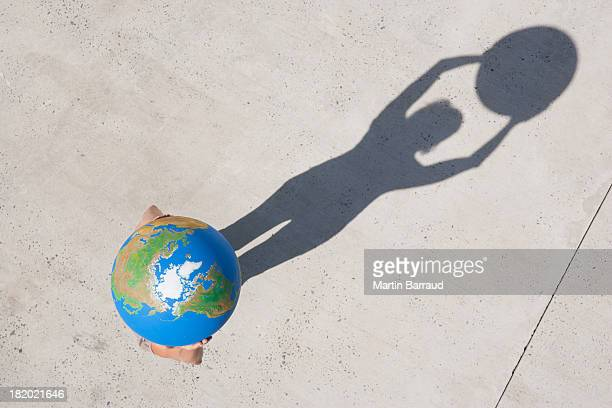 aerial view of person holding globe - world kindness day stock photos and pictures