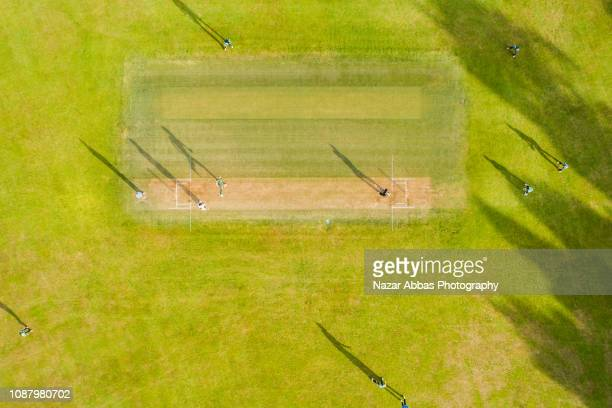 aerial view of players playing in cricket ground. - cricket field stock pictures, royalty-free photos & images