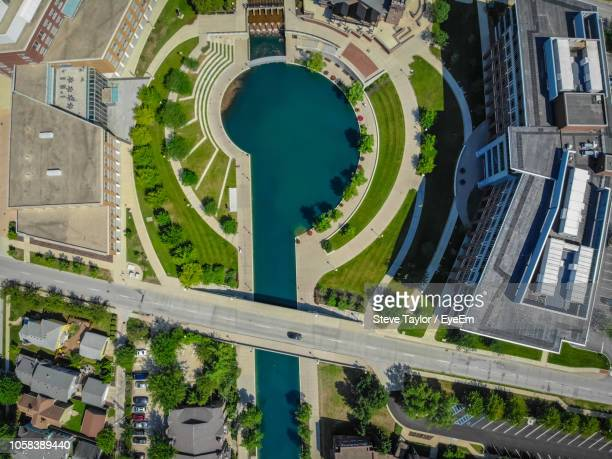 aerial view of pond in park by buildings at city - indiana stock-fotos und bilder