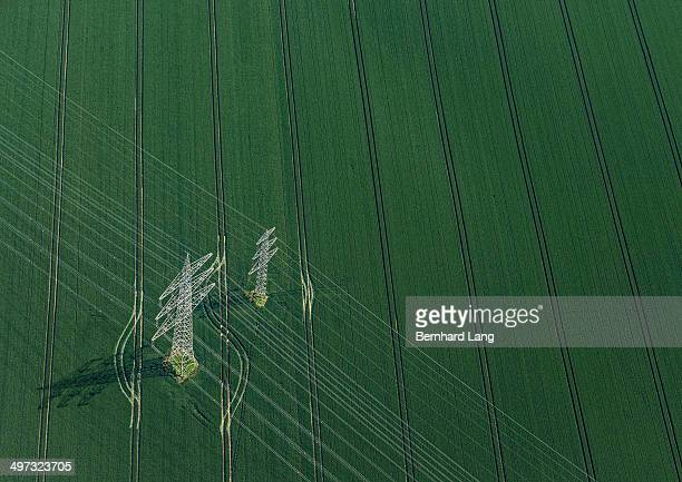 aerial view of power poles on green field - power line stock pictures, royalty-free photos & images