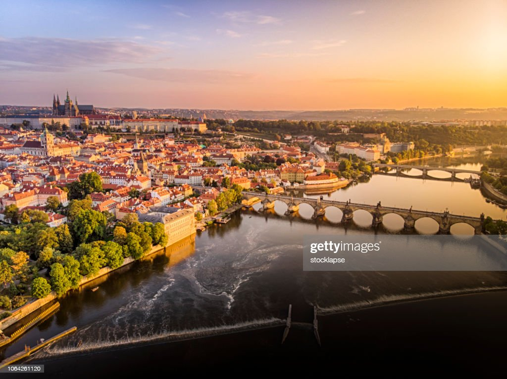 Aerial view of Prague Castle, cathedral and Charles Bridge at sunrise in Prague : Stock Photo