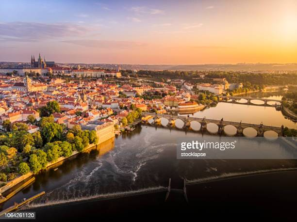 aerial view of prague castle, cathedral and charles bridge at sunrise in prague - prague stock pictures, royalty-free photos & images
