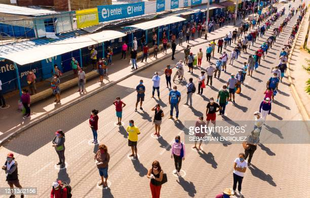 TOPSHOT Aerial view of queues of shoppers maintaining distance as a preventive measure against the novel coronavirus COVID19 outside the municipal...