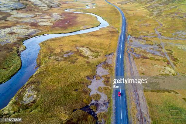 aerial view of red car driving on road in iceland - remote location stock pictures, royalty-free photos & images