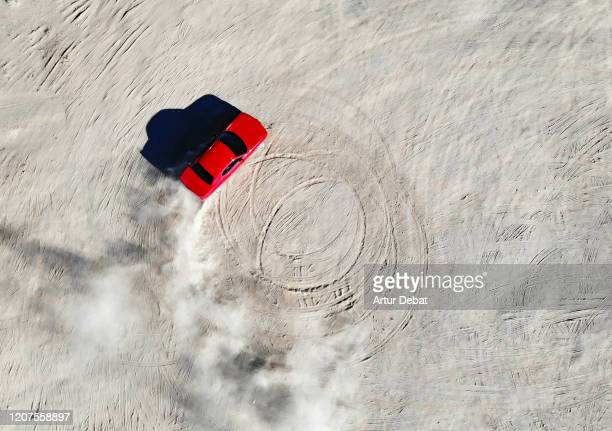 aerial view of red muscle car doing donuts in the desert of california. - american culture stock pictures, royalty-free photos & images