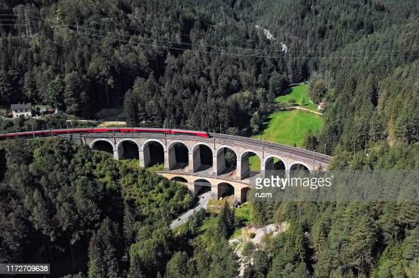 luchtfoto van rode treinritten op het beroemde kalte rinne viaduct op de historische semmering railway (semmeringbahn), neder-oostenrijk. - oostenrijk stockfoto's en -beelden
