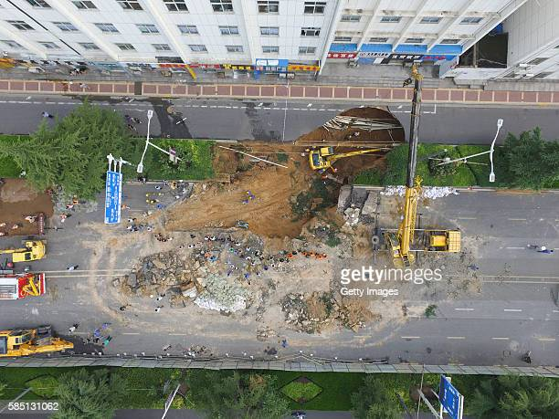 Aerial view of rescuers working at giant hole resulted from road collapse on August 2 2016 in Zhengzhou Henan Province of China Four pedestrians fell...