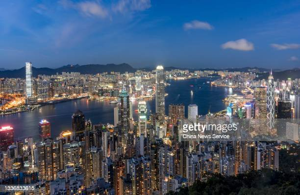Aerial view of residential and commercial buildings being illuminated next to Victoria Harbour at night on August 22, 2021 in Hong Kong, China.