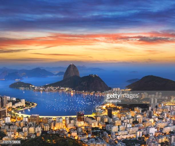 aerial view of rio de janeiro brazil with guanabara bay and sugar loaf at night - rio de janeiro stock pictures, royalty-free photos & images