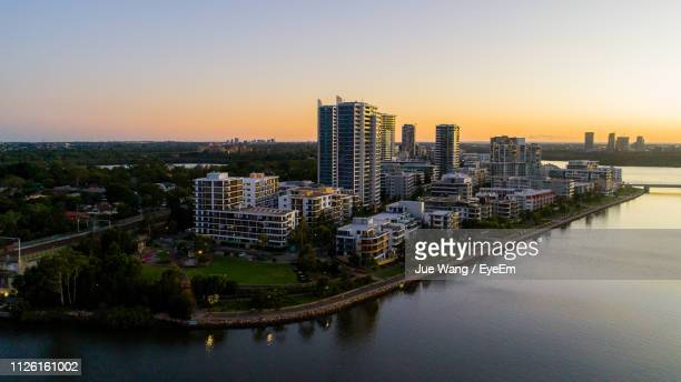 Aerial View Of River Amidst Buildings Against Sky During Sunset