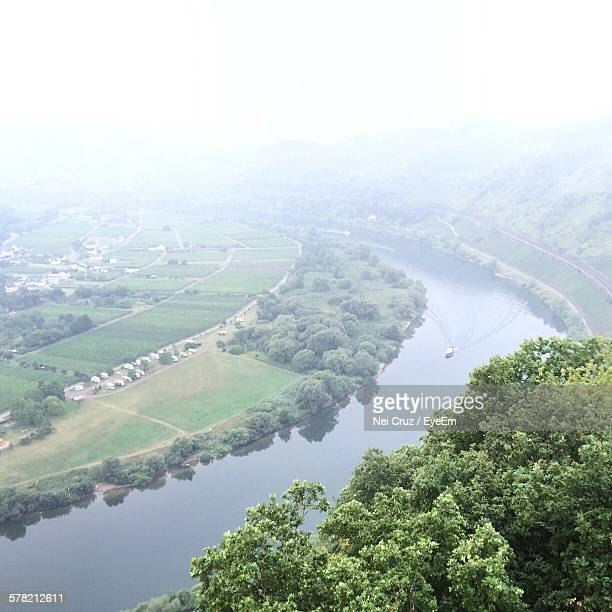 Aerial View Of River Amidst Field Against Sky During Foggy Weather