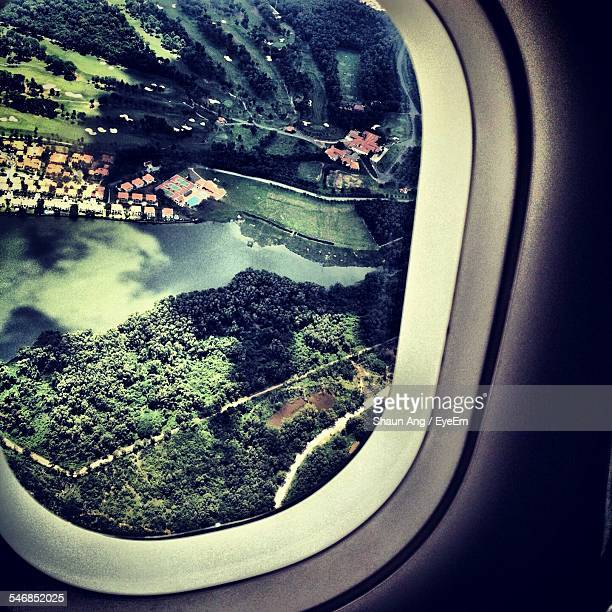 Aerial View Of River And Trees Seen Through Airplane Window