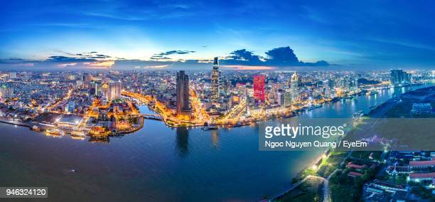 Aerial View Of River By Illuminated City During Sunset