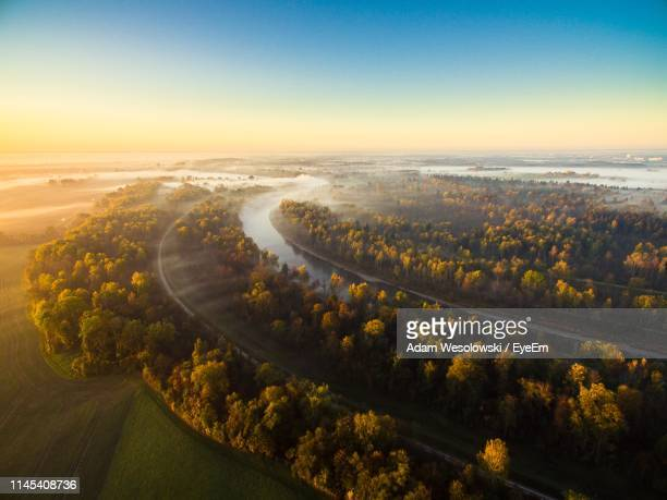 Aerial View Of River In Forest Against Sky During Sunset