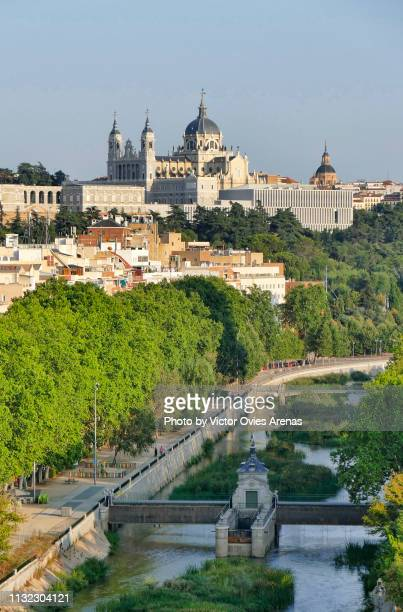 Aerial view of river Manzanares with the Almudena cathedral and the Royal Palace in the background in Madrid, Spain