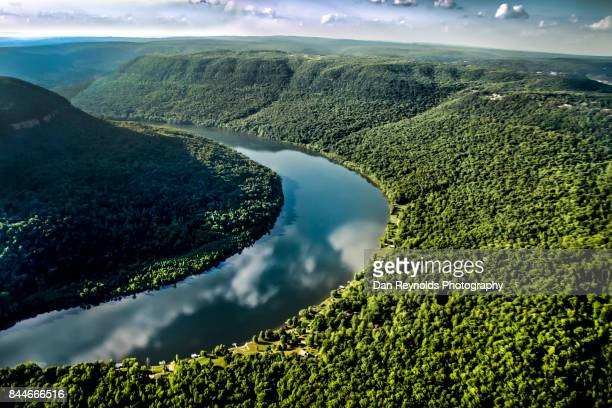 aerial view of river through river gorge with cloud reflections - flowing stock pictures, royalty-free photos & images