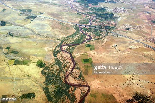Aerial view of  river winding its way across an arid plain.