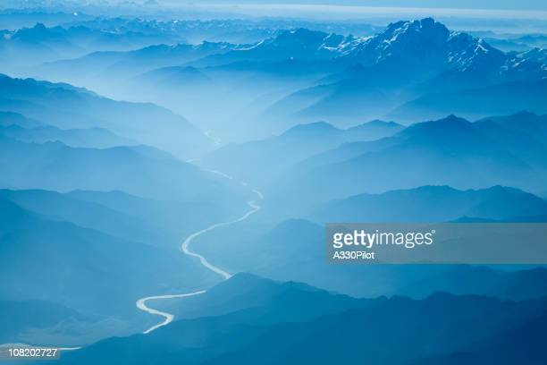 Aerial View of River Winding Through Foggy Himalyan Mountains