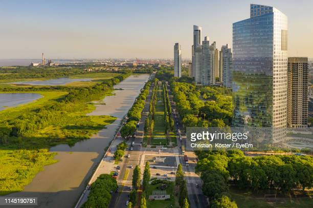 aerial view of river with trees and buildings in city against sky - buenos aires stock-fotos und bilder