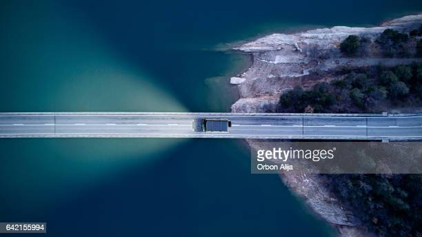 aerial view of road above a lake - thoroughfare stock photos and pictures