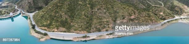 aerial view of road above a lake - dique barragem imagens e fotografias de stock