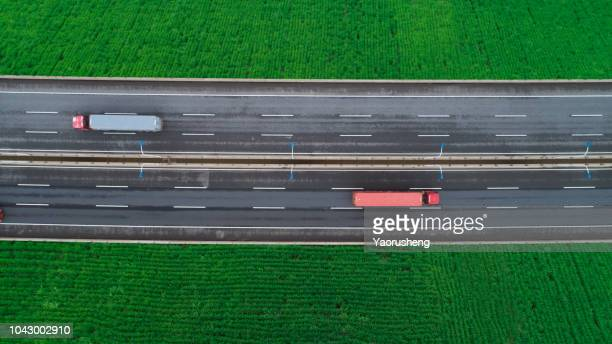 aerial view of road between green meadow - copy space - rushing the field stock pictures, royalty-free photos & images