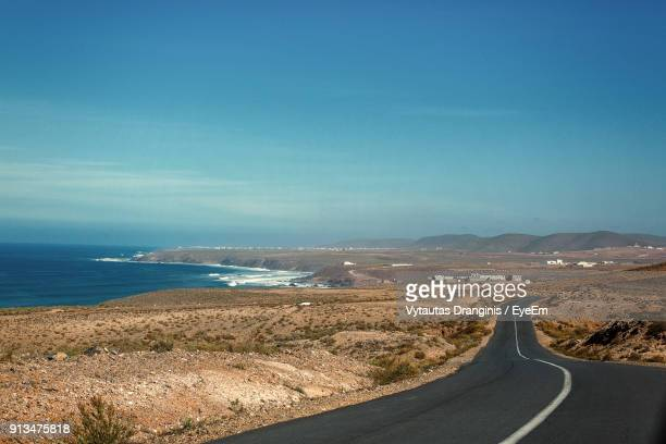 Aerial View Of Road By Sea Against Blue Sky
