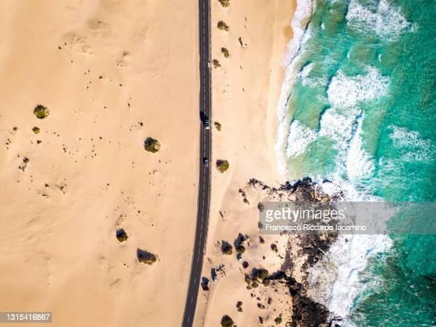 aerial view of road in corralejo near ocean and desert dunes, fuerteventura - francesco riccardo iacomino spain foto e immagini stock