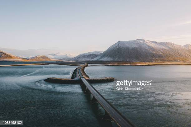 aerial view of road in iceland through the sea - westfjords iceland stock photos and pictures
