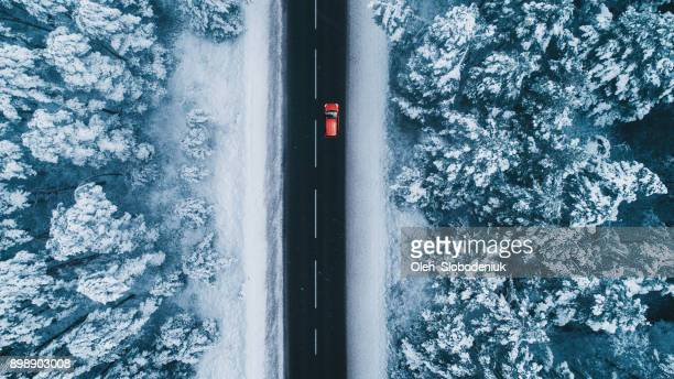 aerial view of road in winter with red car on it - country christmas stock pictures, royalty-free photos & images