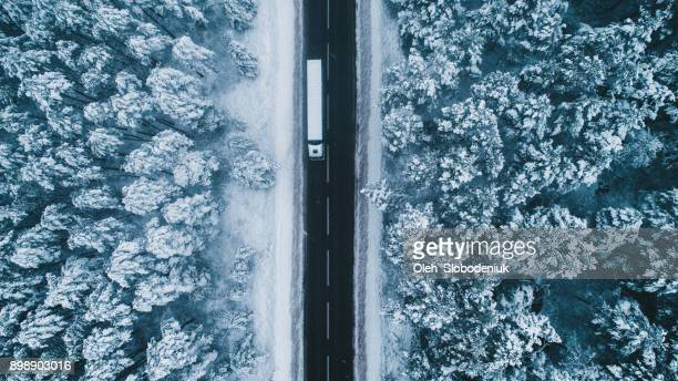 aerial view of road in winter with truck on it - country christmas stock pictures, royalty-free photos & images