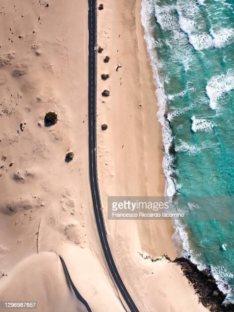 aerial view of road near ocean and corralejo desert dunes, fuerteventura - francesco riccardo iacomino spain foto e immagini stock