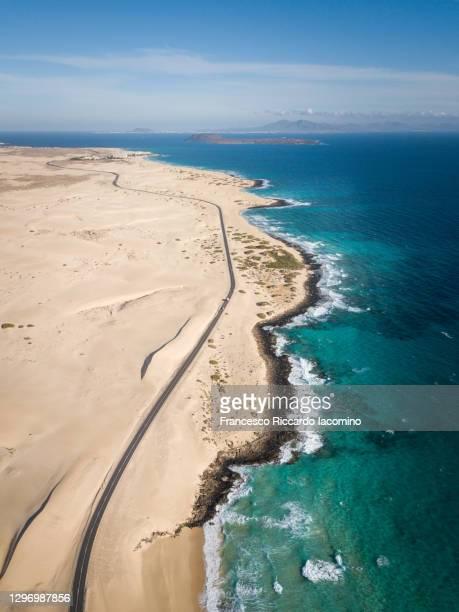 aerial view of road near ocean and desert dunes, corralejo, fuerteventura - francesco riccardo iacomino spain foto e immagini stock