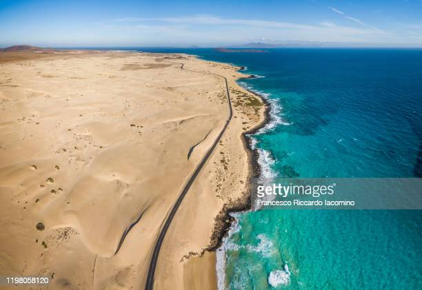 aerial view of road near ocean and desert dunes, fuerteventura - francesco riccardo iacomino spain foto e immagini stock