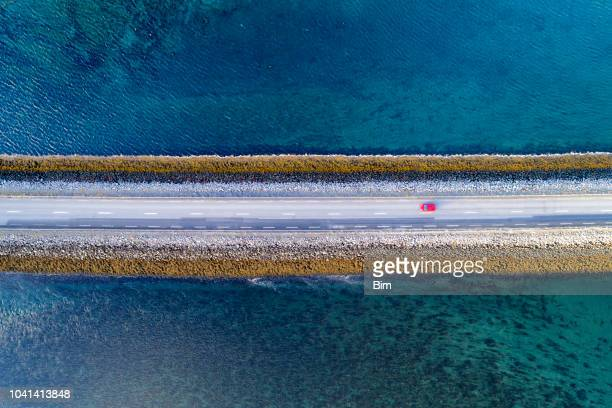 aerial view of road on causeway in iceland - road stock pictures, royalty-free photos & images