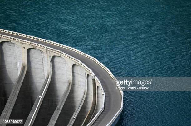 aerial view of road on dam - dam stock pictures, royalty-free photos & images