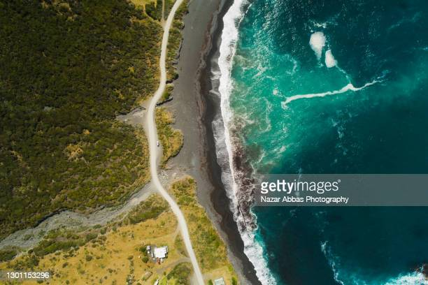 aerial view of road passing next to coast. - sustainable lifestyle stock pictures, royalty-free photos & images