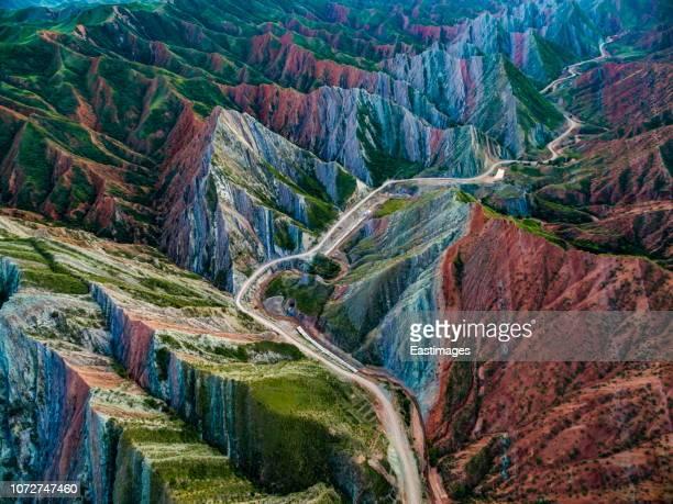 aerial view of road through danxia landform, xinjiang, china - xinjiang stockfoto's en -beelden