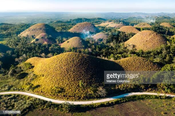 aerial view of road through the chocolate hills, philippines - paisajes de filipinas fotografías e imágenes de stock