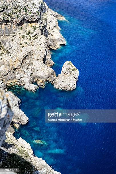 Aerial View Of Rock Formation At Blue Sea