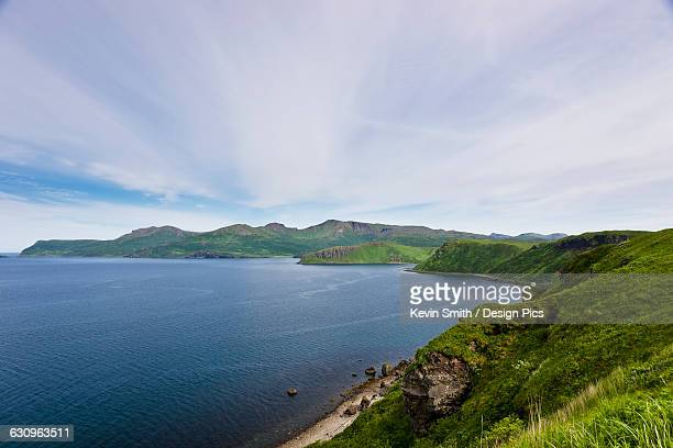 Aerial view of rocky cliffs and green bluffs along the shore of Popof Island near Sand Point, Southwestern Alaska, USA, Summer