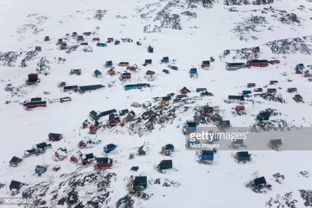 aerial view of rocky winter landscape with small settlement of cottages. - überleben stock-fotos und bilder
