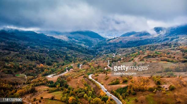flygvy över landsbygdens landskap och slingrande väg i fjäll vildmarken - rumänien bildbanksfoton och bilder