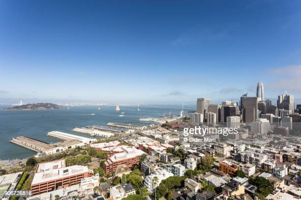 aerial view of san francisco business district with the san francisco oakland bay bridge and the treasure island in the background - didier marti stock photos and pictures